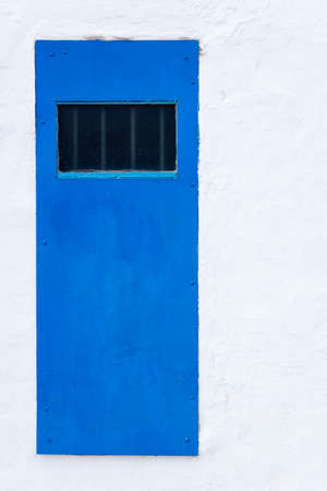 a blue door with bars on a white wall Stock Photo