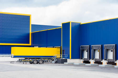 warehouse painted yellow and blue with a trailer in front Stock Photo