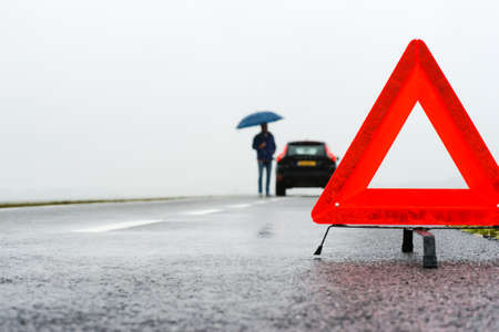 предупреждать: Человек с зонтиком помимо его сломанной машине вместе дороге в середине нигде