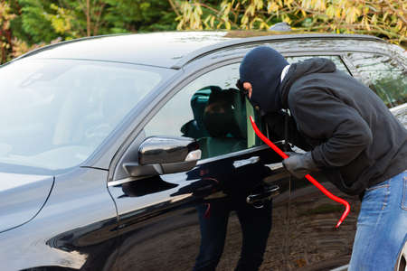 A burglar in action to rob something out of a car photo