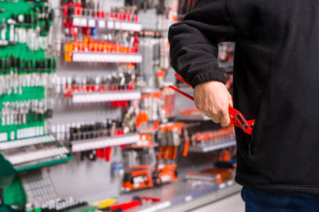 theft prevention: male shoplifter stealing tools in a hardware store