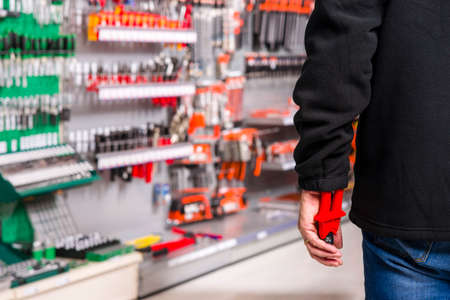 criminal act: male shoplifter stealing tools in a hardware store