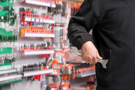 mannelijke winkeldief steelt gereedschap in een ijzerhandel