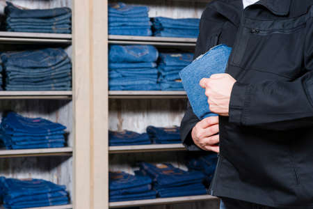 theft prevention: jeans being stolen by a shoplifter in a shop Stock Photo