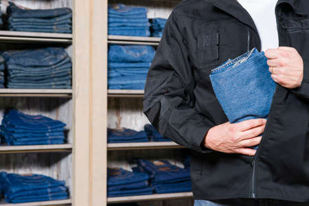 shoplifter: jeans being stolen by a shoplifter in a shop Stock Photo