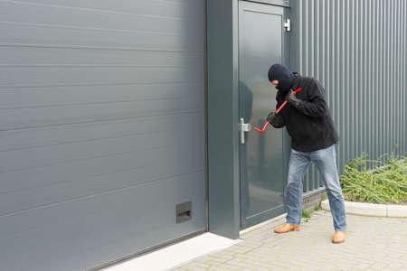 inbreker in vermomming naar een industriële deur te openen met brute kracht Stockfoto