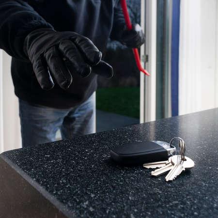 Beteken kijkend inbreker een keuken aan de autosleutel van het aanrecht te pakken