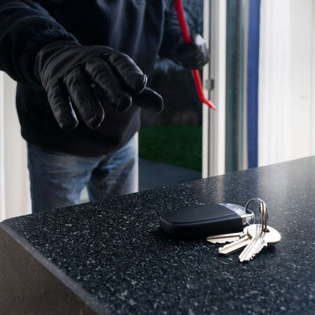 Mean looking burglar enters a kitchen to grab the car key from the kitchen counter Banque d'images