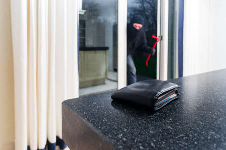 creditcards: Mean looking burglar enters a kitchen to grab a wallet from the kitchen counter