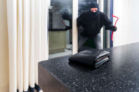 stealing money: Mean looking burglar enters a kitchen to grab a wallet from the kitchen counter