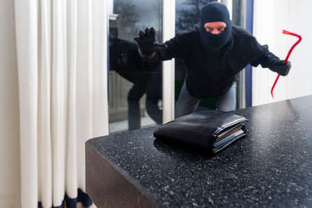 Mean looking burglar enters a kitchen to grab a wallet from the kitchen counter photo