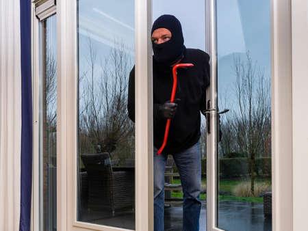 enters: Mean looking burglar enters a kitchen