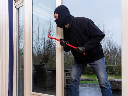 Mean looking burglar enters a kitchen