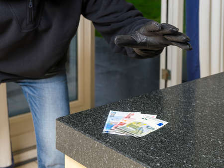 Burglar enters a kitchen to grab money from the kitchen counter