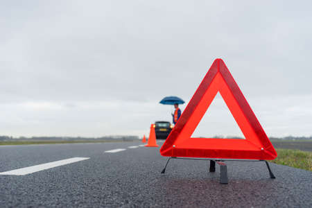 car trouble: man with an umbrella besides his broken car alongside a road in the middle of nowhere