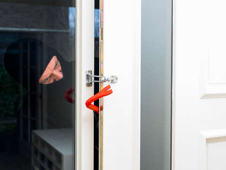 enters: Mean looking burglar enters a house  and forces the door Stock Photo
