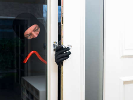 Mean looking burglar enters a house  and forces the door photo