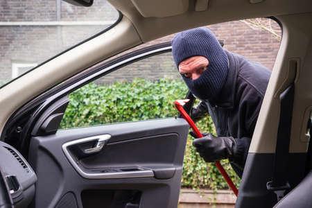 robo de autos: Un ladrón en la acción de robar algo de un coche
