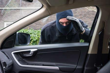 Un ladrón en la acción de robar algo de un coche Foto de archivo - 26037095
