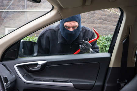 forceful: A burglar in action to rob something out of a car