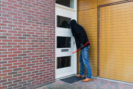 Mean looking burglar enters a house