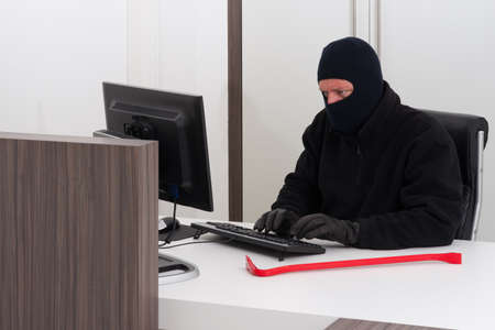 robbing: A burglar is robbing knowledge from a company Stock Photo