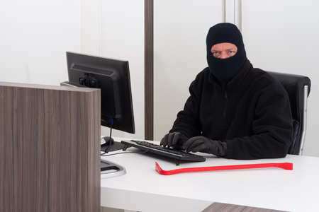 A burglar is robbing knowledge from a company Stock Photo