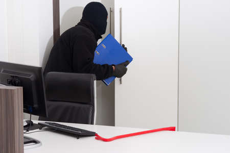 data theft: A burglar is robbing knowledge from a company Stock Photo
