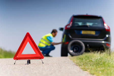 roadside stand: Car with problems and a red triangle to warn other road users