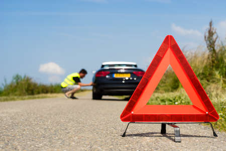 damaged car: Car with problems and a red triangle to warn other road users