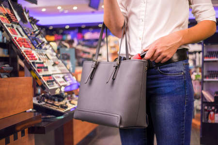 Young woman is stealing goods in a shop