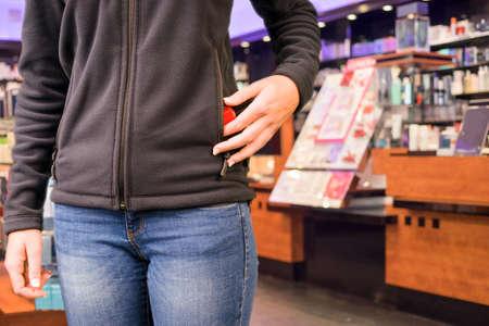 ladron: Mujer joven está robando mercancía en una tienda Foto de archivo
