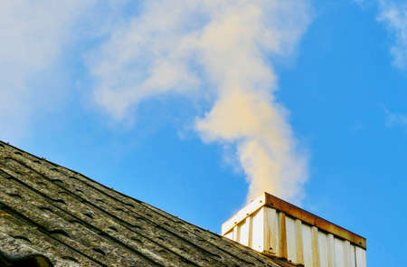smoke rises from the chimney up against a background of blue sky Stock Photo