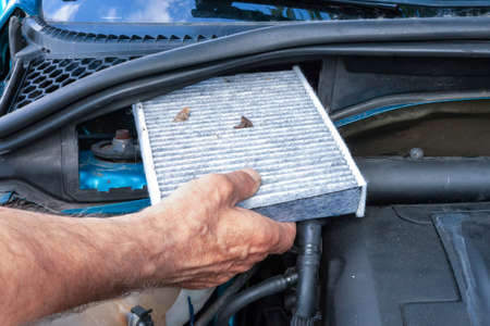 the man pulls out an old dirty cabin filter