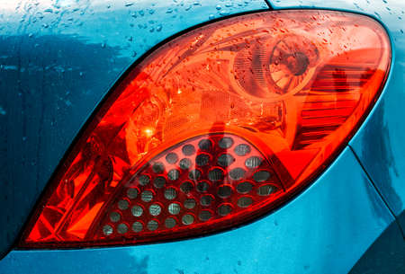 red car headlight with raindrops