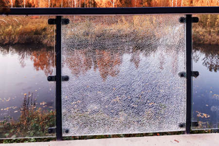 In the park, a glass guard on the river bank in the fall with one broken glass