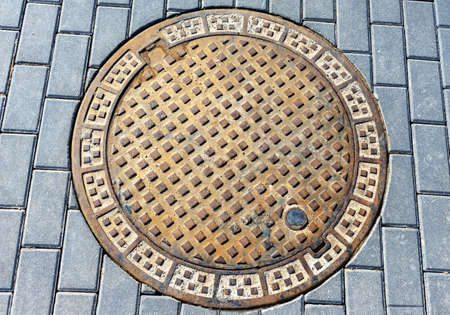 Sewer manhole cover between pavement blocks, top view