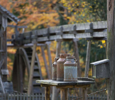 water mill: Three old milk cans on a table, water mill with visible water wheel in the background, autumn colors