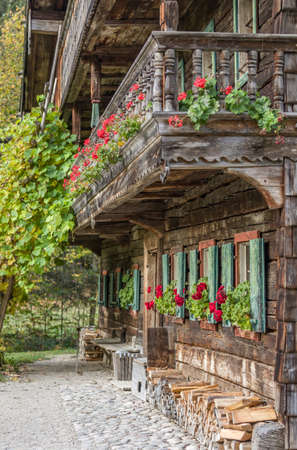 Historic german farmhouse in the alps. Front side with red flowers.