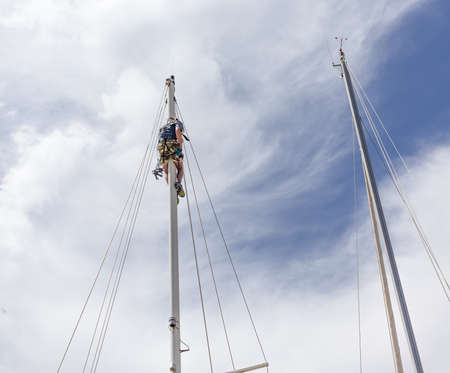 Rigger in a sailboat mast attaching steps