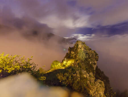 menton: Long exposure of a rocky hill in the french alps (near Menton), lit by the moon and a streetlight. Stock Photo