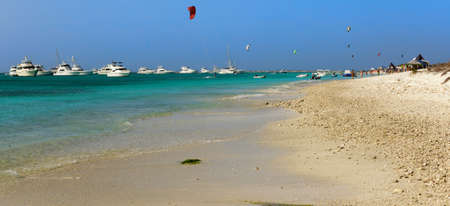 Kite surfing in the caribbean, beach scene with huts and motor yachts. Crasqui, Los Roques, Venezuela