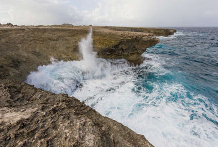 Surf and spray at caribbean coast, Bonaire. Blue an turquoise water at rocks. Stock Photo
