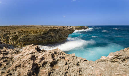 Surf at caribbean coast, Bonaire. Blue and turquoise water at rocks. Long exposure, water looks dynamic. Stock Photo