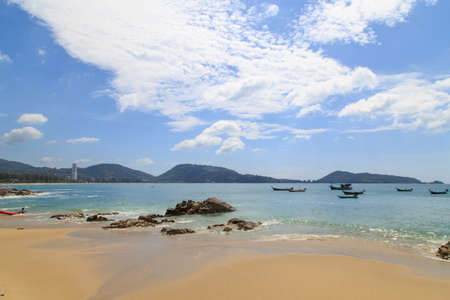 Beautiful beach under sunshine in andaman sea/The beach and blue sky clouds/Fishing boat on the beach in phuket Thailand/At kalim beach neary Patong beach phuket Thailand/
