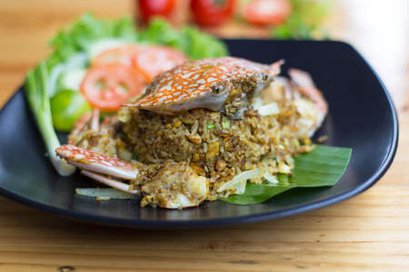 Fried rice with crab on dish with spoonCrab fried rice with curry powder,onionKao pad poo