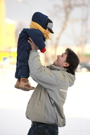 toss: father toss up the child to on the snow in winter Stock Photo