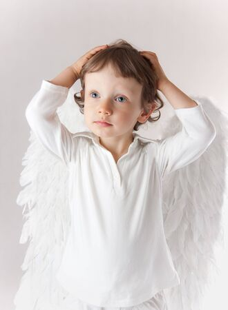 Beautiful little angel boy, white clothes, wings, blue eyes photo