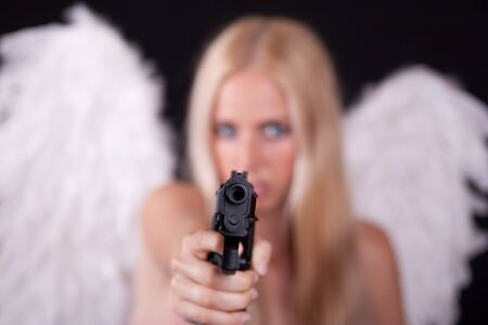 Angel with white wings, aiming weapon in his arm.  Black background. photo