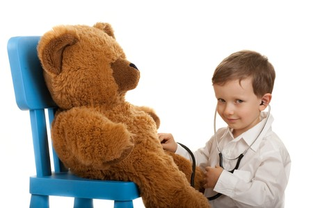 doctor toys: Child playing in doctor with stethoscope examination teddybear.